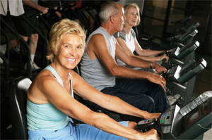 Older people on stationary bikes