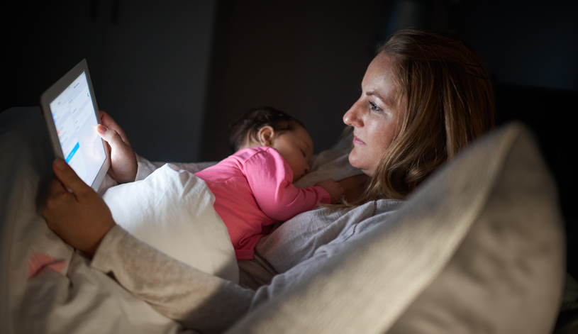 Mom using tablet and holding baby at night