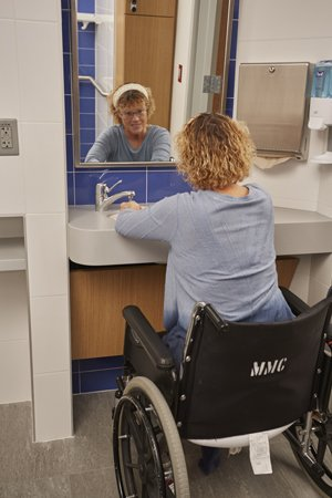 Bathroom includes a tilted mirror for easier use among those in wheelchairs or those who cannot stand for long periods of time.