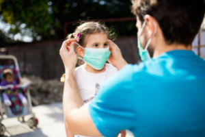 father putting mask on child