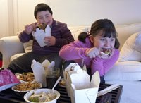 Kids eating takeout and watching TV