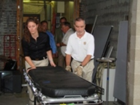 Anne Obrecht, administrative intern at Mercy Medical Center in Cedar Rapids, helps Gary Pacha, an Iowa City Rotarian, load a patient treatment cart onto a truck Aug. 21.  Mercy donated used and surplus medical equipment to the Rotary group, which will send the items to areas of Central America where donated medical supplies are in great demand.