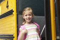Girl next to a school bus
